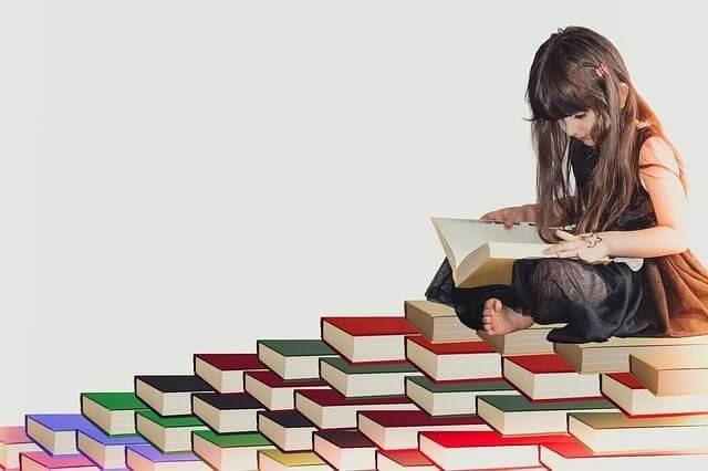 たくさんの本の上で読書をする少女