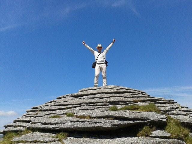 山頂に立ち両腕を挙げる男性
